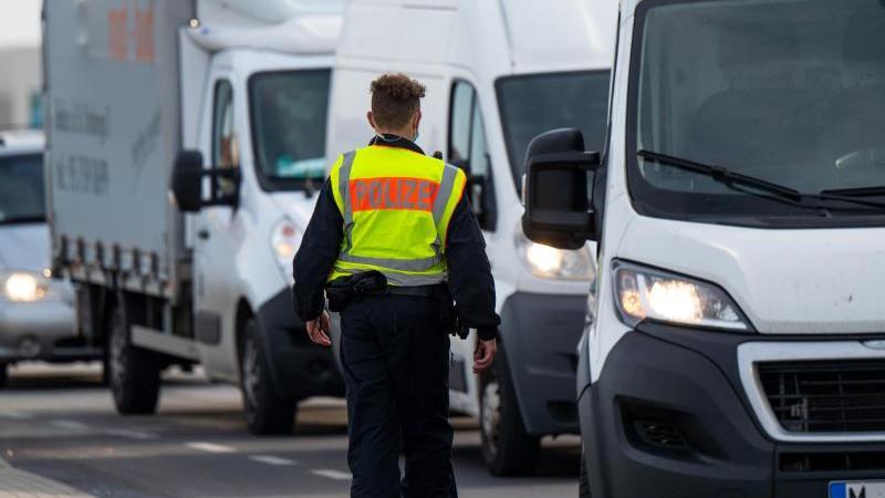 ein-polizist-halt-auf-der-grenzbrucke-zwischen-deutschland-und-polen-fahrzeuge-an-foto-monika-skolimowskadpa-zentralbilddpaarchivbild