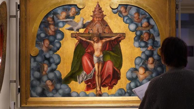 eine-frau-betrachtet-das-werk-hl-dreifaltigkeit-1515-1520-im-st-annen-museum-foto-marcus-brandtdpa