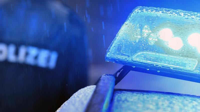 ein-polizist-steht-vor-einem-streifenwagen-mit-blaulicht-foto-karl-josef-hildenbranddpasymbolbild