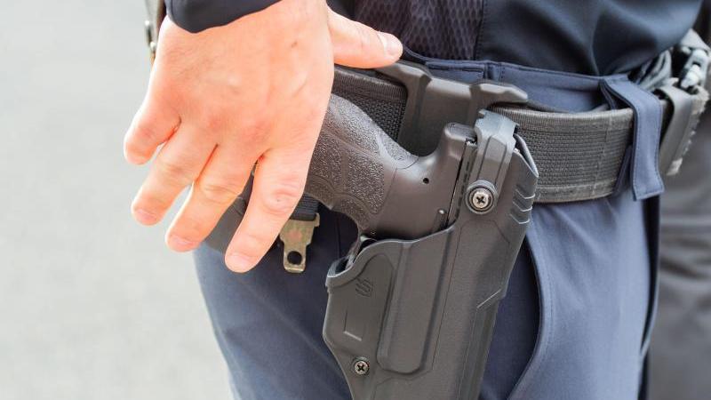 ein-polizist-greift-nach-seiner-waffe-foto-julian-stratenschultedpasymbolbild