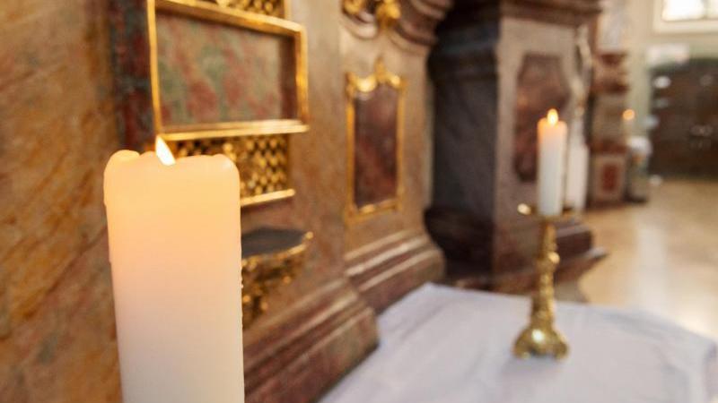 Kerzen brennen vor dem Sonntagsgottesdienst. Foto: Silas Stein/dpa/Symbolbild