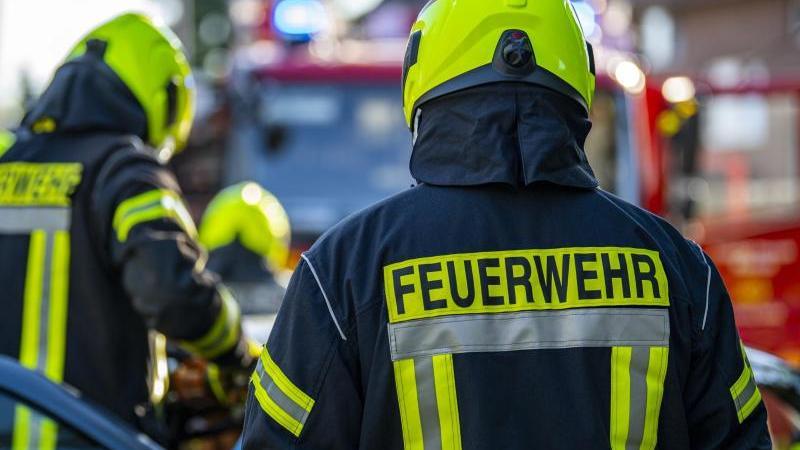 Feuerwehrleute stehen um ein Auto, das einen Unfall gehabt hat. Foto: David Inderlied/dpa/Symbolbild