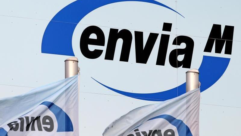 Zwei Fahnen wehen vor dem Logo des Chemnitzer Energieversorgers EnviaM in Halle (Saale). Foto: Jan Woitas/dpa-Zentralbild/dpa