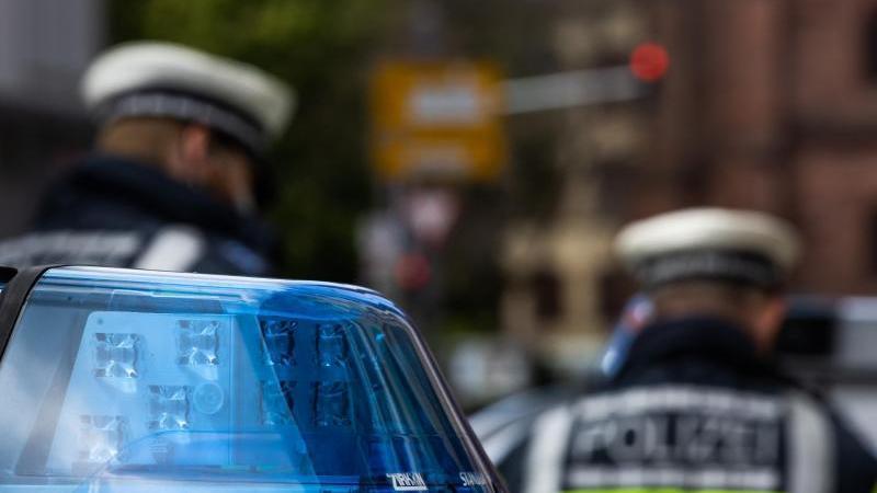 zwei-polizeibeamte-stehen-zwischen-einsatzfahrzeugen-foto-philipp-von-ditfurthdpasymbolbild