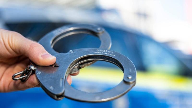 eine-hand-halt-handschellen-vor-einen-streifenwagen-der-polizei-foto-david-inderlieddpaillustration