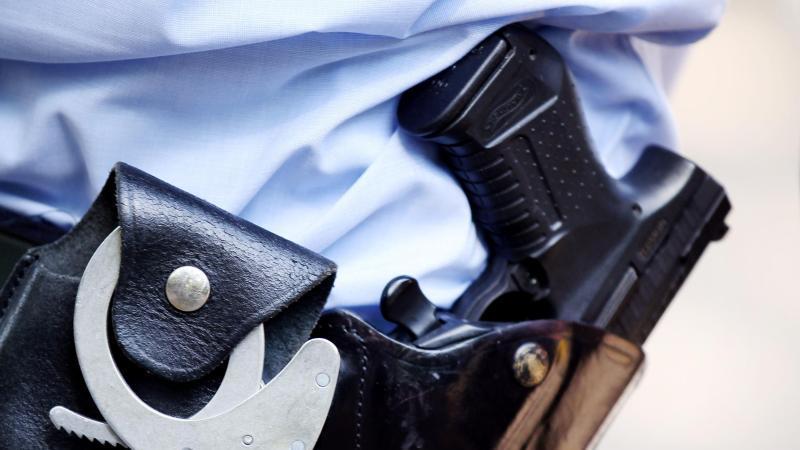ein-polizist-mit-handschellen-und-pistole-am-gurtel-foto-oliver-bergdpa