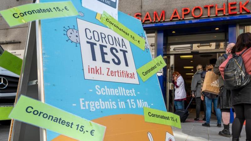 passanten-stehen-vor-einer-apotheke-die-einen-corona-test-fur-15-euro-anbietet-foto-peter-kneffeldpaarchivbild