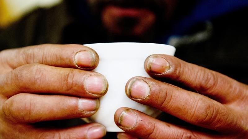 ein-wohnungsloser-mann-halt-in-einem-nachtcafe-ind-dresden-eine-tasse-foto-sebastian-kahnertzbdpa