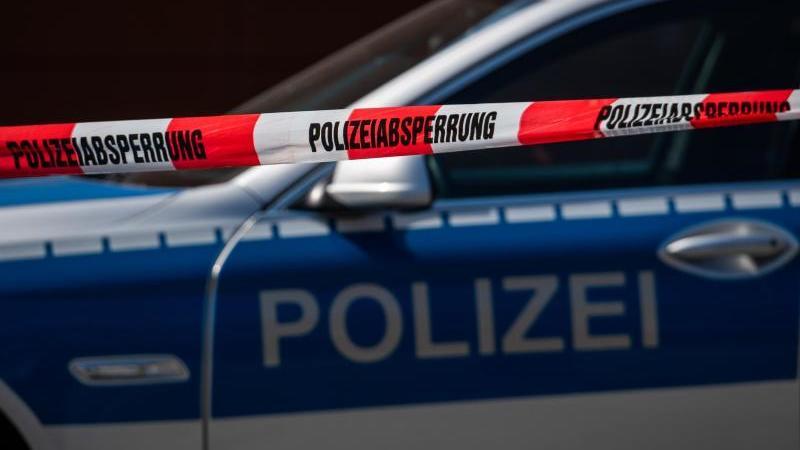 ein-polizeiauto-steht-hinter-einem-absperrband-foto-robert-michaeldpa-zentralbilddpasymbolbild