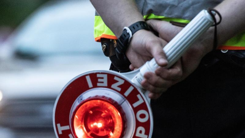 ein-polizist-halt-bei-einer-verkehrskontrolle-eine-winkerkelle-in-der-hand-foto-paul-zinkendpazbsymbolbild