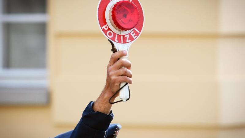 ein-polizist-halt-eine-winkerkelle-in-der-hand-foto-soeren-stachedpa-zentralbilddpasymbolbild