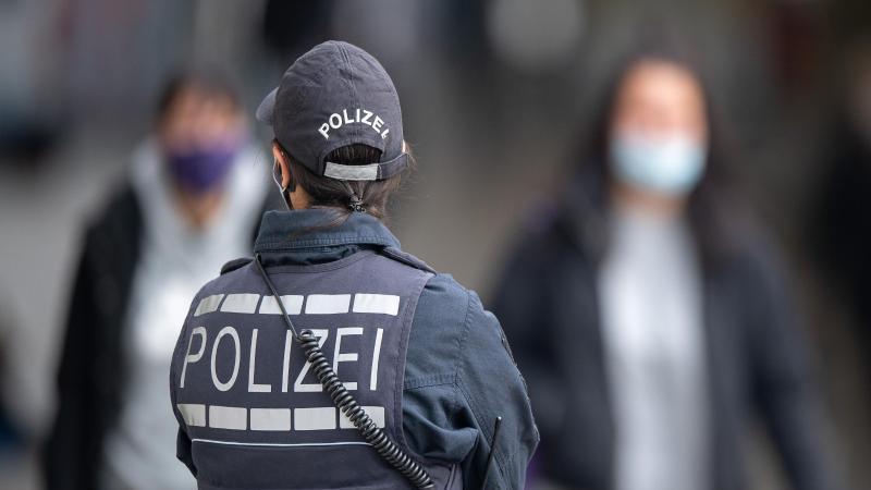 eine-polizistin-blickt-zu-passanten-mit-masken-foto-sebastian-gollnowdpasymbolbild