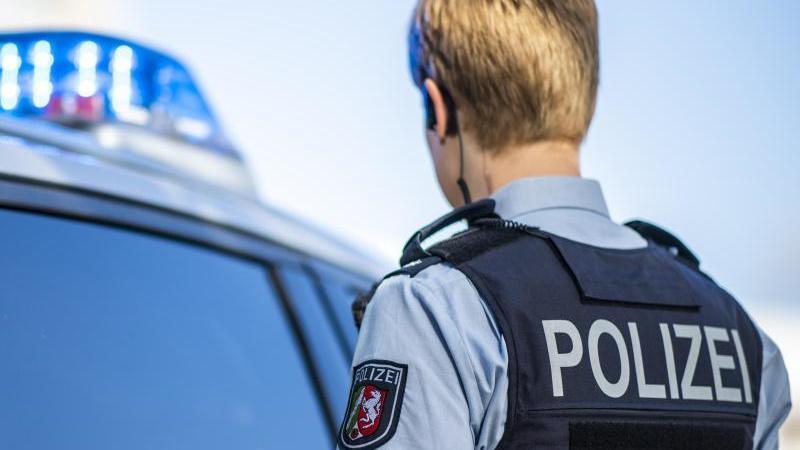 eine-polizistin-steht-vor-einem-streifenwagen-foto-david-inderlieddpaillustration