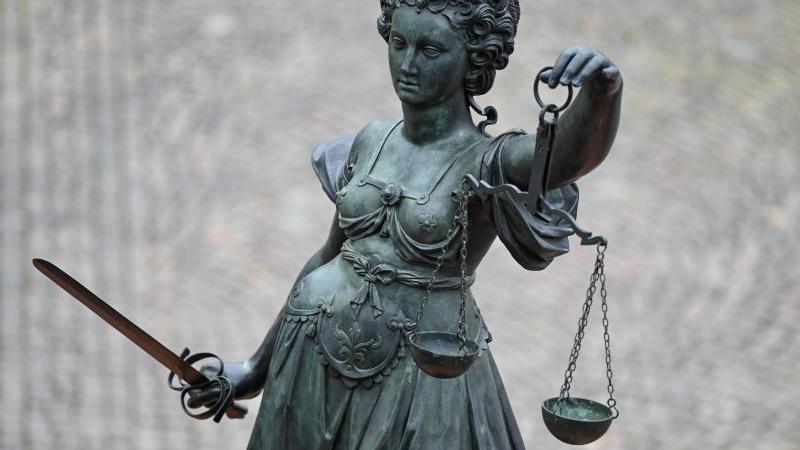 eine-statue-der-justitia-halt-eine-waage-und-ein-schwert-in-der-hand-foto-arne-dedertdpasymbolbild