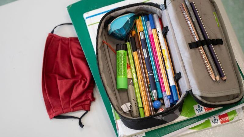 eine-atemschutzmaske-liegt-neben-einem-federmappchen-foto-marijan-muratdpasymbolbild