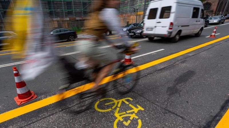 ein-radfahrer-fahrt-uber-einen-pop-up-radweg-in-munchen-foto-peter-kneffeldpaarchivbild