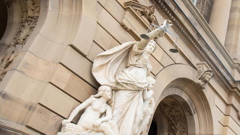 vor-einem-gericht-halt-eine-statue-der-justitia-eine-waagschale-foto-stefan-puchnerdpasymbolbild