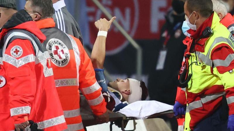 der-nurnberger-tom-krau-m-wird-verletzt-aus-dem-stadion-getragen-zeigt-aber-mit-dem-daumen-nach-oben-foto-daniel-karmanndpa