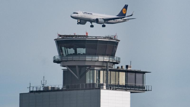 eine-passagiermaschine-der-lufthansa-fliegt-hinter-dem-tower-foto-boris-roesslerdpa