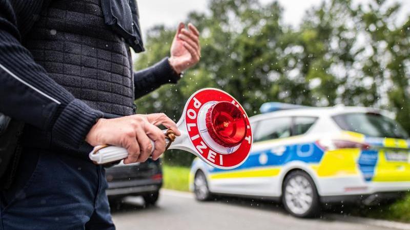 eine-polizistin-halt-eine-winkerkelle-in-der-hand-foto-guido-kirchnerdpasymbolbild