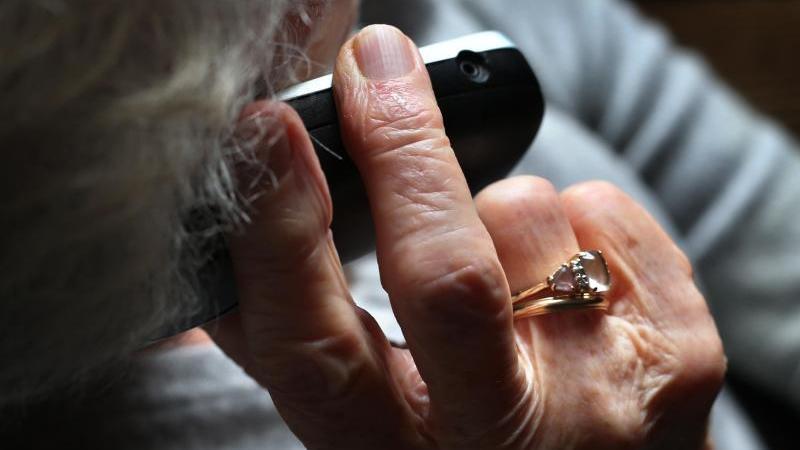 eine-rentnerin-halt-ein-telefon-in-der-hand-foto-karl-josef-hildenbranddpasymbolbild