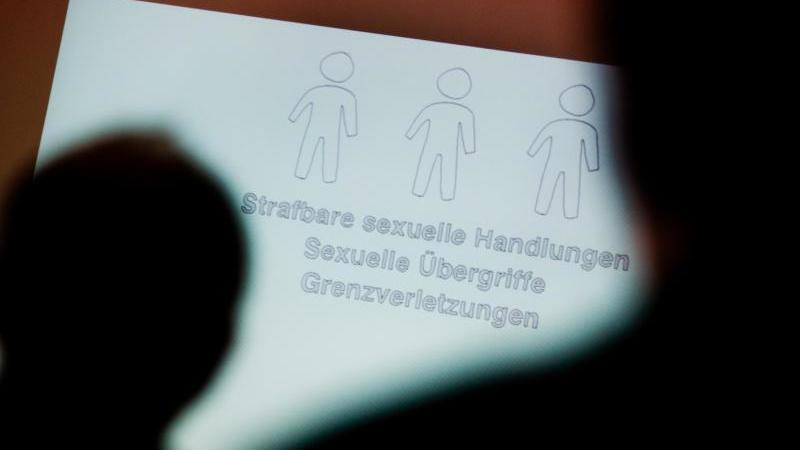 teilnehmer-betrachten-bei-einer-fachtagung-zur-pravention-von-sexuellem-missbrauch-eine-prasentation-foto-julian-stratenschultedpaillustration