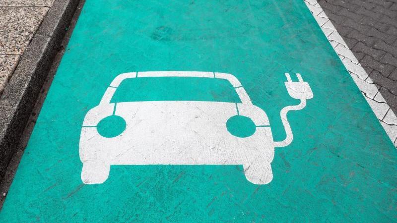 ein-auto-auf-einem-grunen-grund-markiert-einen-parkplatz-mit-ladesaule-fur-elektrofahrzeuge-foto-jan-woitaszbdpaarchivbild