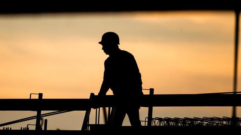 die-silhouette-eines-bauarbeiters-zeichnet-sich-auf-einer-baustelle-vor-dem-morgenhimmel-ab-foto-julian-stratenschultedpasymbolbild