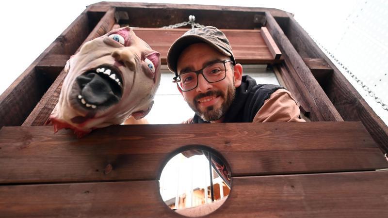 marcel-lang-steht-an-seinem-haus-an-einer-nachgebauten-guillotine-mit-einem-halloween-totenkopf-foto-uli-deckdpa