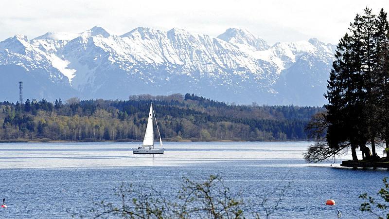 Eines der ersten Segelboote gleitet am Donnerstag (26.04.2012) vor der Kulisse der verschneiten Alpen bei Tutzing (Oberbayern) über den Starnberger See. Laut Wetterbericht herrscht in den nächsten Tagen in Bayern weiterhin hochsommerliches Wetter. Fo