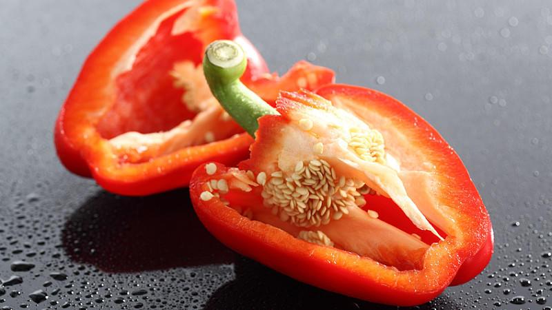 Die kleinen Samen der Paprika verteilen sich beim Aufschneiden überall.