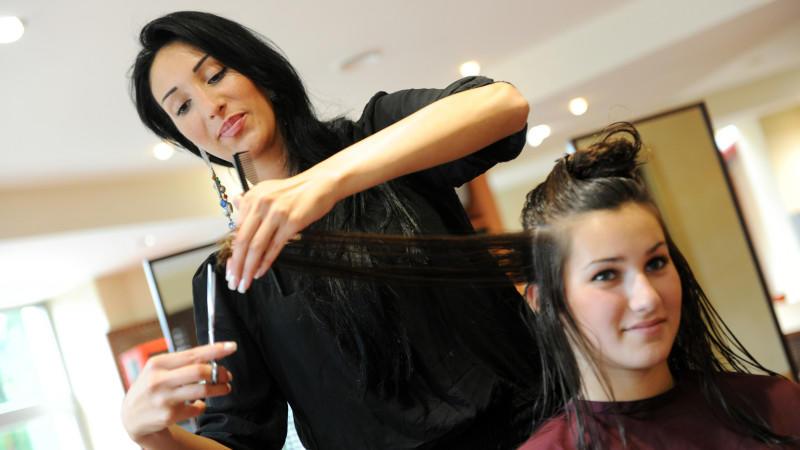 Friseurin schneidet Haare einer Kundin.