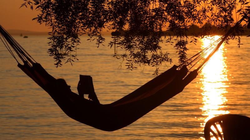 Eine Frau liest am Samstag (20.08.2011) in einer Hängematte am Badestrand eines Campingplatzes in Lindau (Schwaben) ein Buch. Ideales Strand- und Badewetter herrscht derzeit am Bodensee. Die Temperaturen steigen bis auf 32 Grad. Foto: Karl-Josef Hild