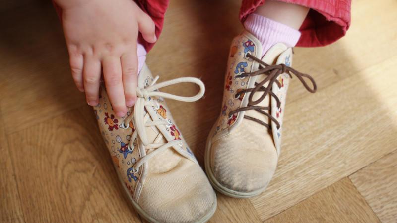 Ein Kind (ein kleines Mädchen) trägt ein Paar stark abgetragene Schuhe aus Stoff mit verschiedenen Schnürsenkeln in Frankfurt am Main am 22.04.2009 (gestelltes Foto zur Illustration).