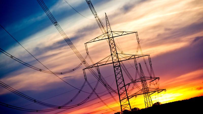 Strommasten vor einem Sonnenuntergang - Senkung der Öko-Umlage minimal