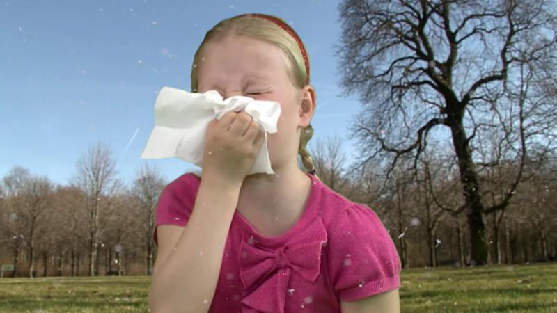 Mädchen niest im Freien in ein Taschentuch