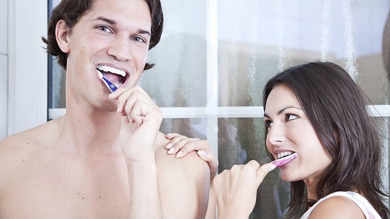 Junges Paar putzt sich die Zähne