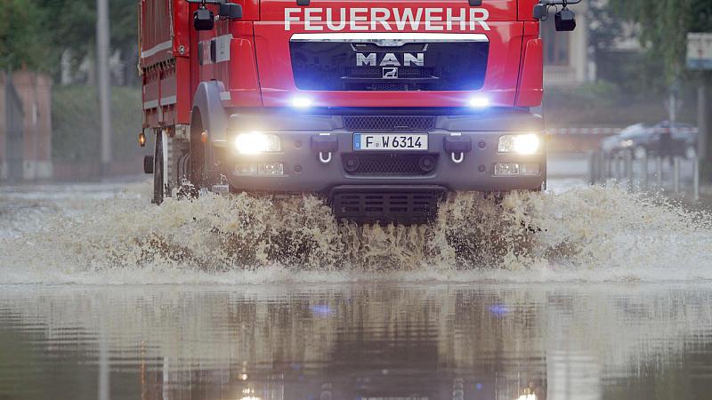 Die Feuerwehr fährt durch eine überflutete Straße in Wiesbaden