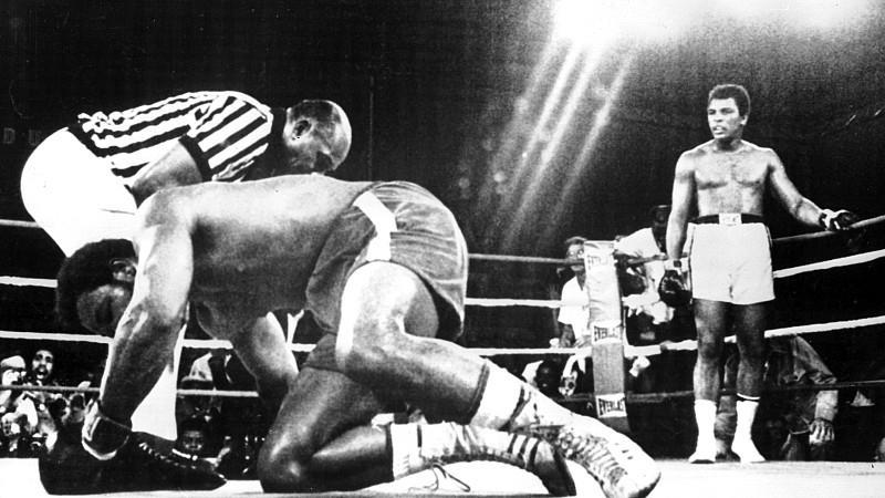 ARCHIV - US-Schwergewichtsboxer Muhammad Ali (r, hinten) steht in der 8. Runde in der neutralen Ecke, sein K.o. geschlagener Kontrahent George Foreman (l, vorn) hat Mühe, wieder auf die Beine zu kommen und wird vom Ringrichter ausgezählt. Ali holt si