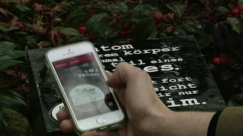 Smartphone scannt QR-Code eines Grabsteins