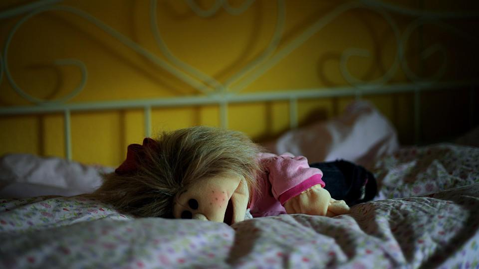 Auf einem Kinderbett liegt eine Stoffpuppe.