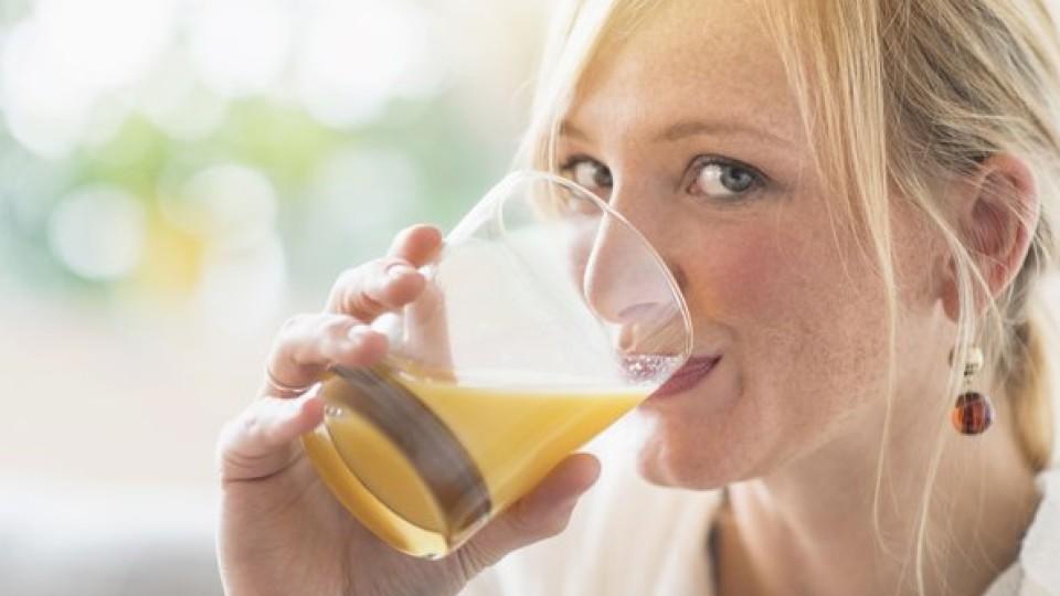 Woman sitting in living room and drinking orange juice, Frau, die im Wohnzimmer sitzt und Orangensaft trinkt