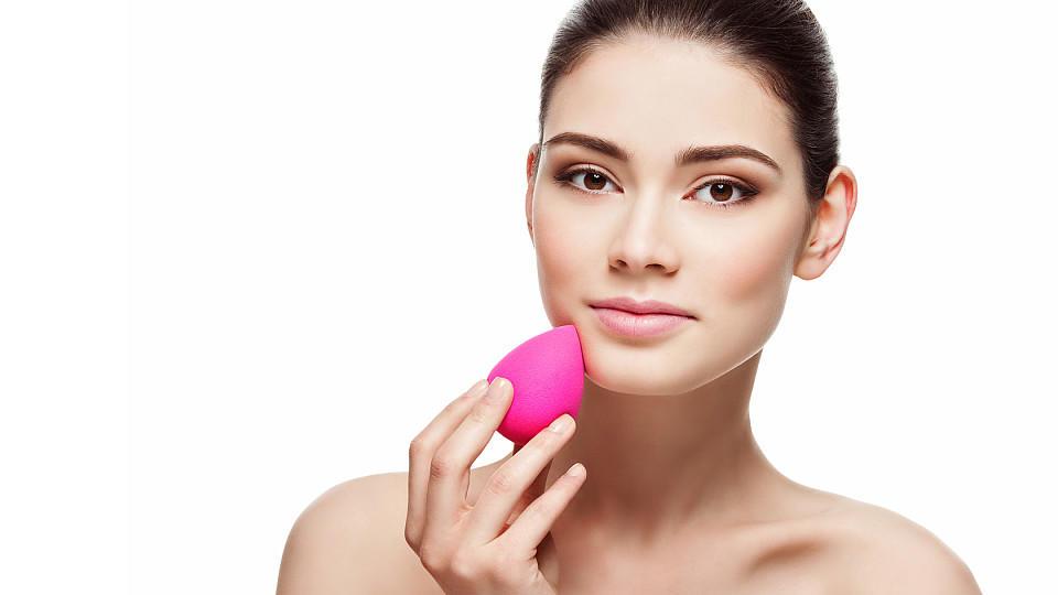Frau trägt Make-up mit Make-up-Ei auf