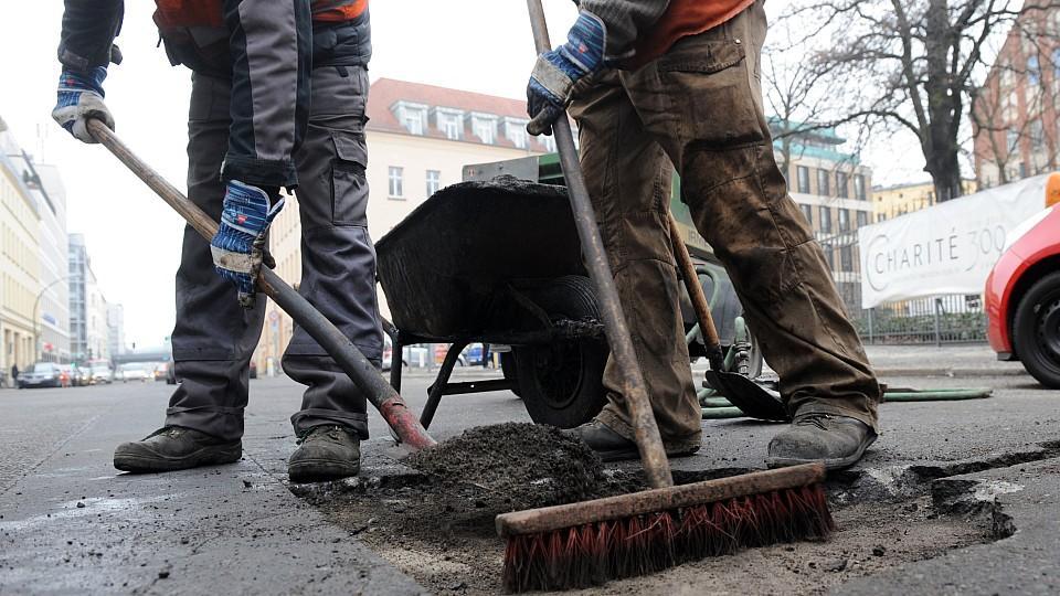 Straßenarbeiter bessern ein Schlagloch aus.