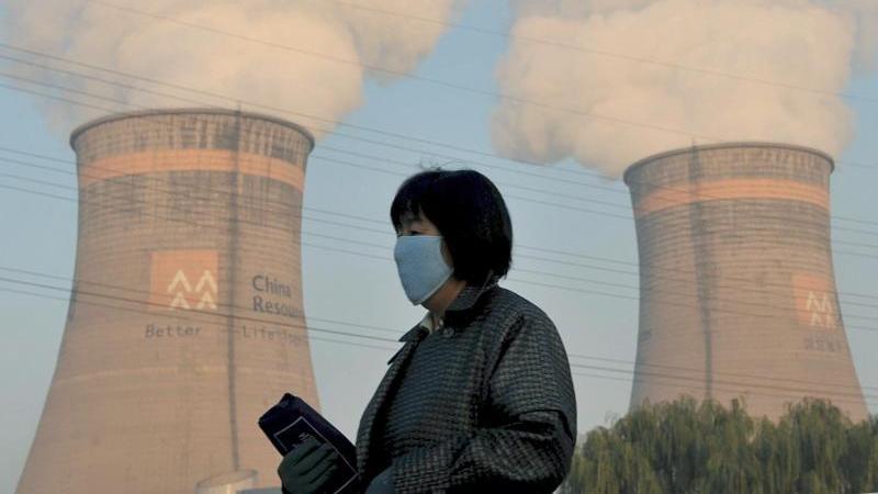 Eine Anwohnerin geht am Kühlturm eines Kohle-Heizkraftwerks in Shenyang im Nordosten Chinas vorbei.