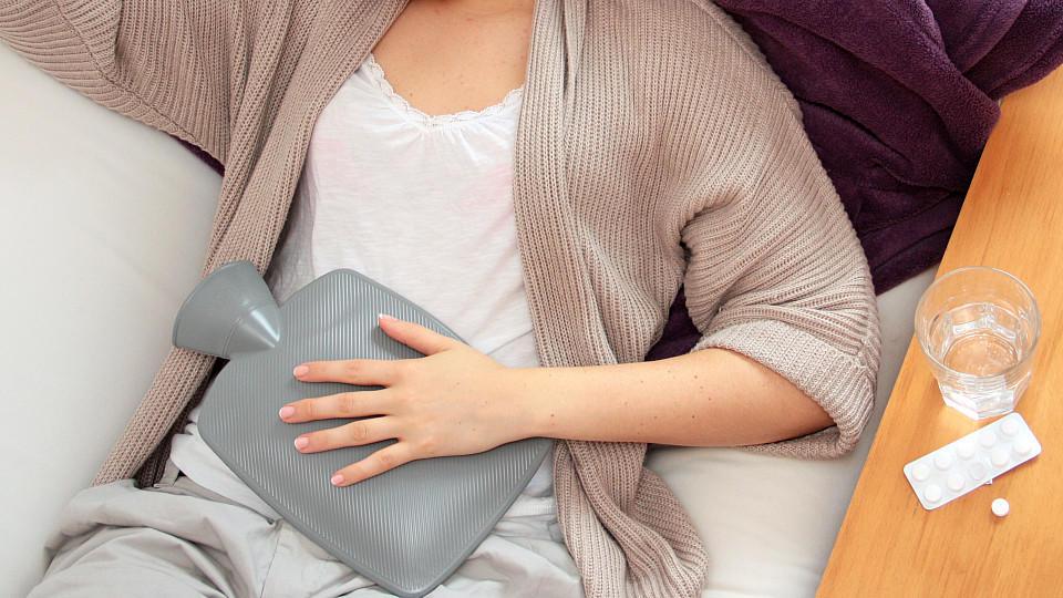 Eine junge Frau liegt am 07.08.2011 in Berlin mit einer Wärmflasche auf dem Bauch auf einem Sofa.