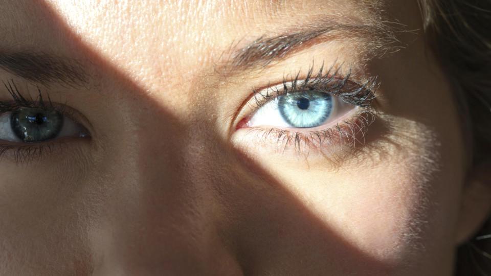 Eine junge Frau mit blauen Augen schaut in die Sonne.