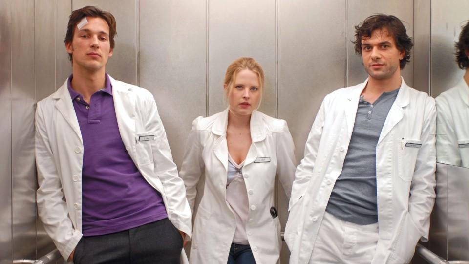 """Dr. Gretchen Haase (Diana Amft) steht bei """"Doctor's Diary"""" zwischen zwei Männern"""