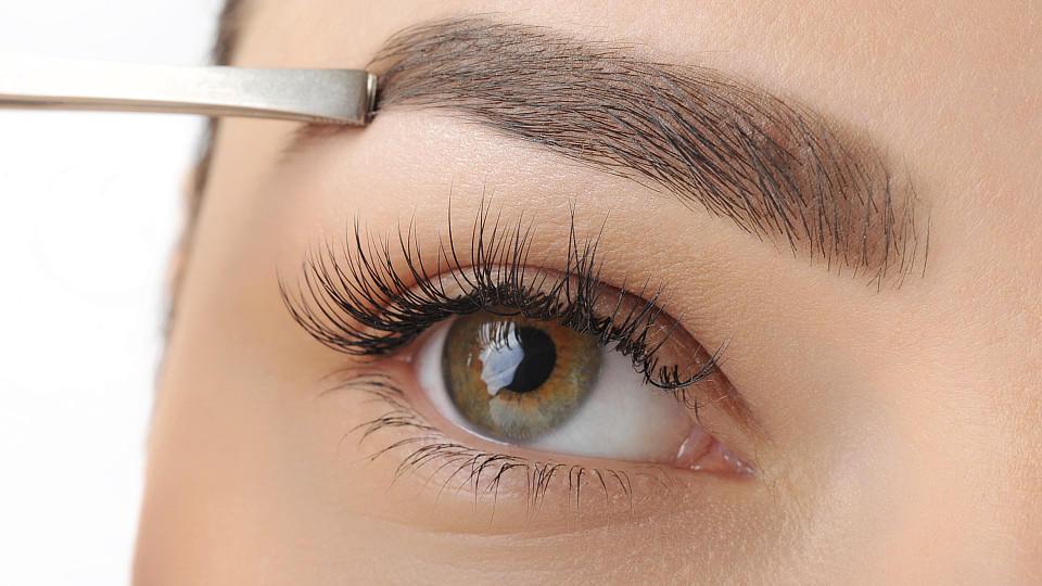 Frau zupft ihre Augenbrauen