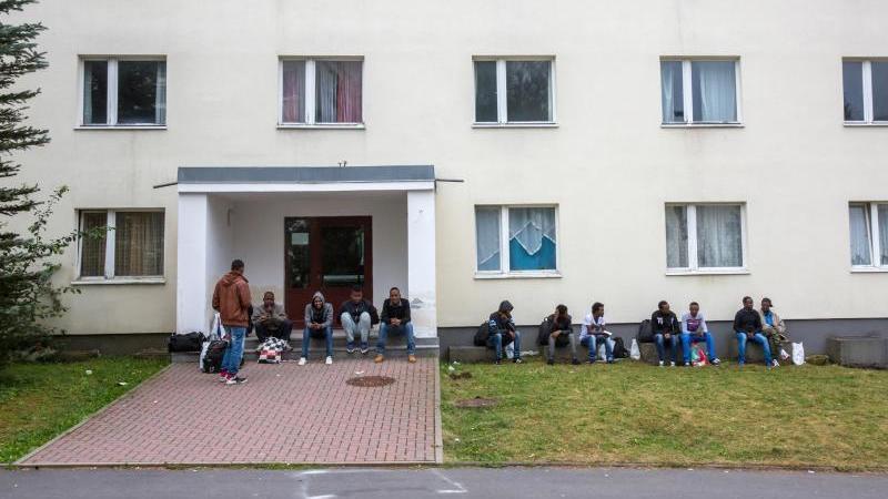 Flüchtlinge sitzen vor einem Wohnblock